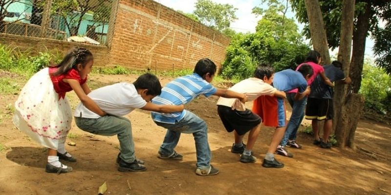 Descripción de foto - niños jugando al arranca cebollas en un parque natural, abrazados de un poste. - Crédito de foto - Viajes de un chapín