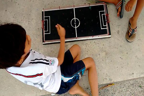Descripción de foto - niños jugando con el futillo de tabla en el piso. - Crédito de foto - Willy Willy