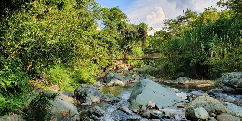 Descripción de foto - vista de las rocas y el agua del Río Hato y, por encima, un puente colgante conocido como la hamaca. - Crédito de foto - InfantiaN