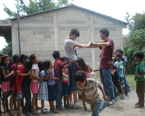 Descripción de la foto para personas con discapacidad visua - Niños jugando con adultos y pasando por debajo de la campana. - Crédito de foto - Grace in Guatemala