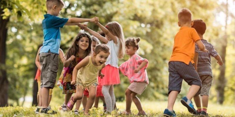 Descripción de la foto para personas con discapacidad visua - Niños pasando por debajo de otros con las manos extendidas. - Crédito de foto -Guía infantil