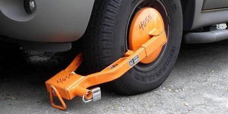 Descripción de la foto para personas con discapacidad visual - Acercamiento de la llanta de un auto en la calle con cepo.- Crédito de foto - La Prensa de Occidente