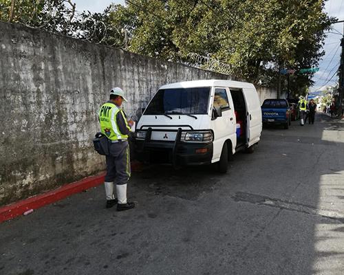 Descripción de la foto para personas con discapacidad visual - Agente de emetra colocando una multa por estacionarse en línea roja.- Departamento de Tránsito de la Policía Municipal