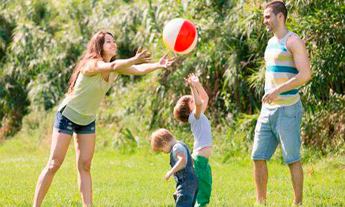 Descripción de la foto para personas con discapacidad visual - Familia jugando zopilote en un jardín. - Crédito de foto - Todo Papás