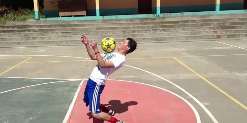Descripción de la foto para personas con discapacidad visual - Hombre levantando la pelota en una cancha.- Crédito de foto - Aldea el Rodeo San Marcos