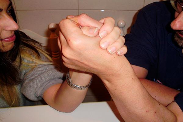 Descripción de la foto para personas con discapacidad visual - Hombre y mujer jugando pulso de manos cara a cara.- Crédito de foto - Psygan
