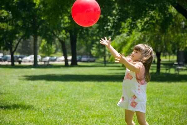 Descripción de la foto para personas con discapacidad visual - Niña atrapando una pelota en el aire.- Crédito de foto - Baby Sparks