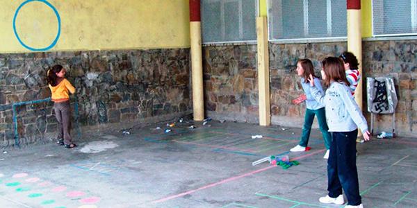 Descripción de la foto para personas con discapacidad visual - Niñas detenidas mientras otra las observa pegada por la pared. - Crédito de foto - AF2Toral