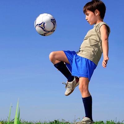 Descripción de la foto para personas con discapacidad visual - Niño haciendo fintas con la pierna mientras rebota la pelota.- Crédito de foto - Guía infantil