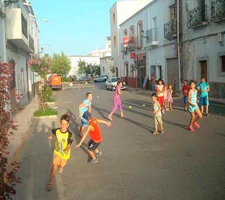 Descripción de la foto para personas con discapacidad visual - Niños corriendo en las calles de unos detrás de otro. - Crédito de foto - Hoy los Ángeles