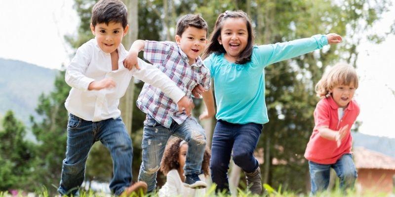 Descripción de la foto para personas con discapacidad visual - Niños corriendo en un campo abierto. - Crédito de foto - Efecto Ezpiral