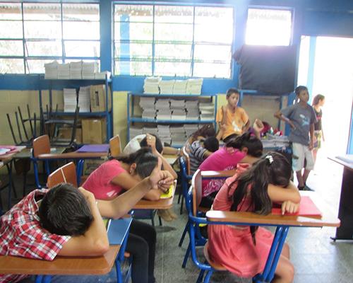 Descripción de la foto para personas con discapacidad visual - Niños en un salón recostados en sus pupitres boca abajo con el dedo levantado. - Crédito de foto - Chicos and Kids Inc