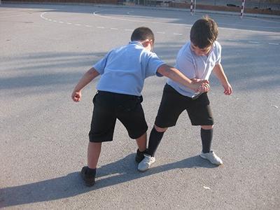 Descripción de la foto para personas con discapacidad visual - Niños jugando pulso de pies y manos en una cancha. - Crédito de foto - Juegos de tiempo libre