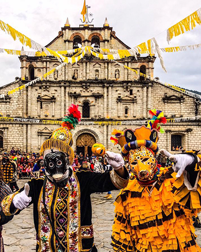 Descripción de la foto para personas con discapacidad visual - Personas vestidas para el baile de los negritos frente a la iglesia de Panajachel. - Crédito de foto - Eduardo Rodríguez
