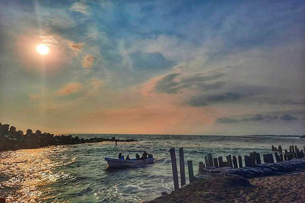 Descripción de la foto para personas con discapacidad visual - Vista de las aguas de la playa de Champerico con unas personas en bote al horizonte. - Crédito de foto - erickwilsoncom