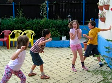 Descripción de la foto para personas con discapacidad visual- niños jugando 1, 2, 3 cruz roja, y otro niño tocando la pared - Crédito de foto - Educación Física Bilingue en Primaria