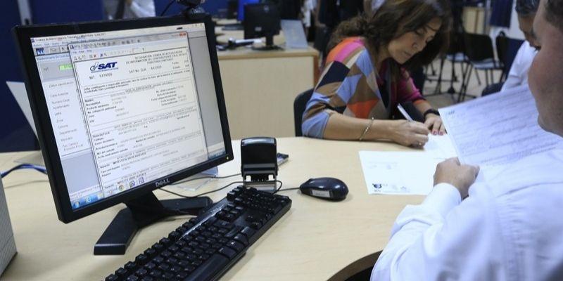 Descripción de la foto para personas con discapacidad visual: mujer firmando unos documentos en una agencia de la SAT. (Crédito de foto: Delta Asesores)